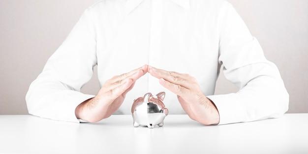 그의 손으로 돼지 저금통을 저장하는 남자. 금융, 위기 및 돈 절약의 개념,