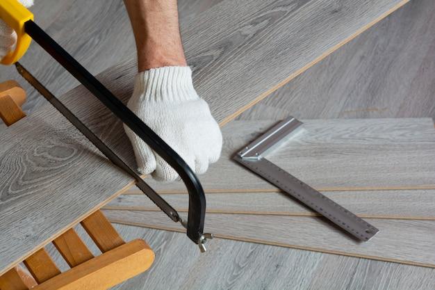 Man sawing gray laminate