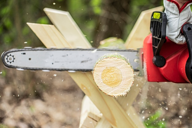 Man sawing wood with a chain saw using sawhorse close up domestic work