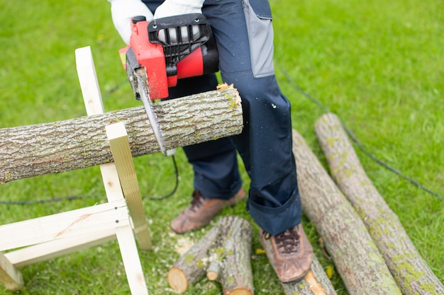 Man sawing wood with a chain saw using sawhorse close up