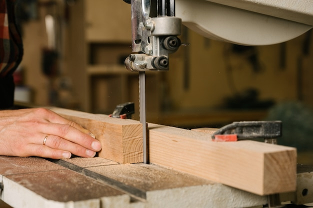 Man sawing a wooden board on a band saw, close up