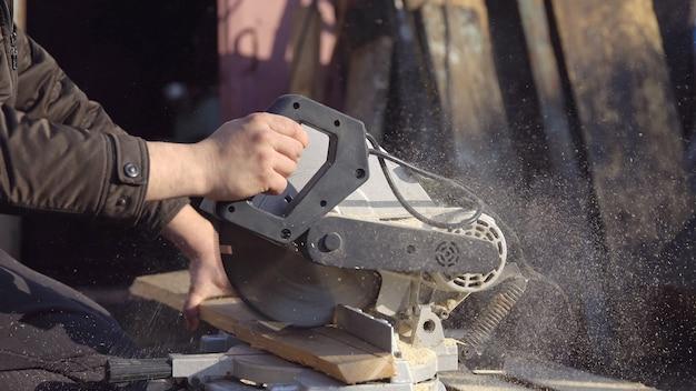 남자는 원형 톱으로 보드를 톱질하고 열심히 일합니다.