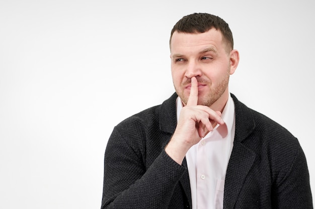 Man saying hush and be quiet with finger on lips gesture