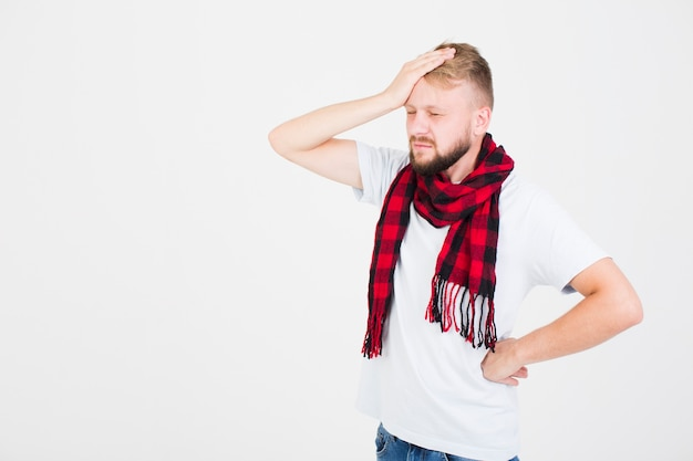 Man in scarf having headache