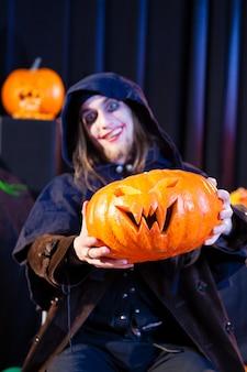 Man in scary halloween costume holding pumpkin
