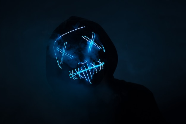 A man in a scary neon glowing mask and a hood on a dark wall with smoke. horror and halloween concept