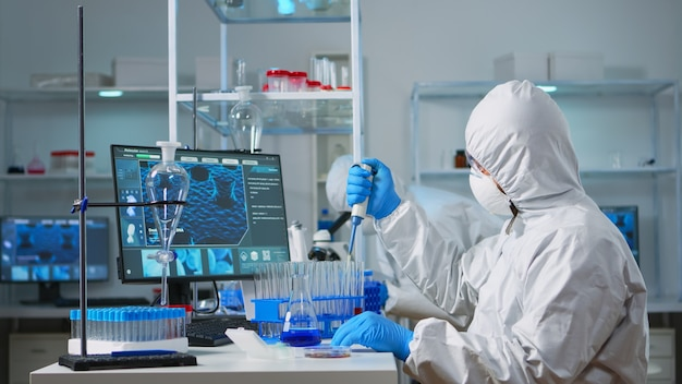 Man scientist in coverall using micropipette in modern equipped laboratory. team of doctors examining vaccine evolution with high tech and chemistry tools for research in development of covid19 virus