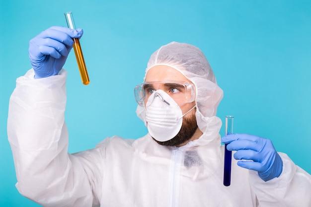 Человек-ученый в защитном костюме и держит пробирки