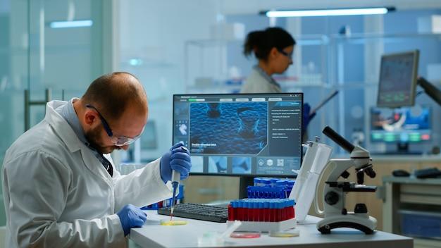 현대적인 시설을 갖춘 실험실에서 시험관을 채우기 위해 마이크로피펫을 사용하는 남자 과학자. covid19에 대한 백신 개발을 위해 첨단 기술을 사용하여 바이러스 진화를 조사하는 연구원 팀