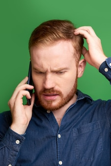 Man scratching head when talking on phone