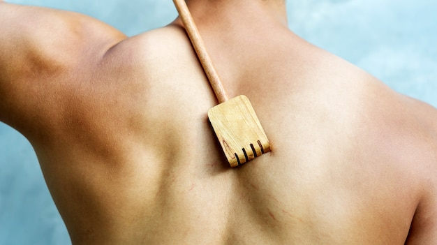 Man scratching his back with a wooden backscratcher