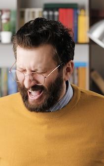 男は悲鳴を上げる。オフィスやアパートの眼鏡をかけたひげを生やした男が目を閉じて悲鳴を上げる。クローズアップビュー