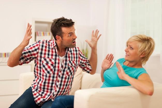 Мужчина кричит на жену во время спора дома