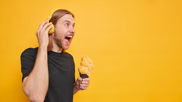 Man screams loudly opens mouth yells from anger has red beard and hair holds delicious ice cream dressed in casual black t shirt listens music via headphones isolated on yellow wall
