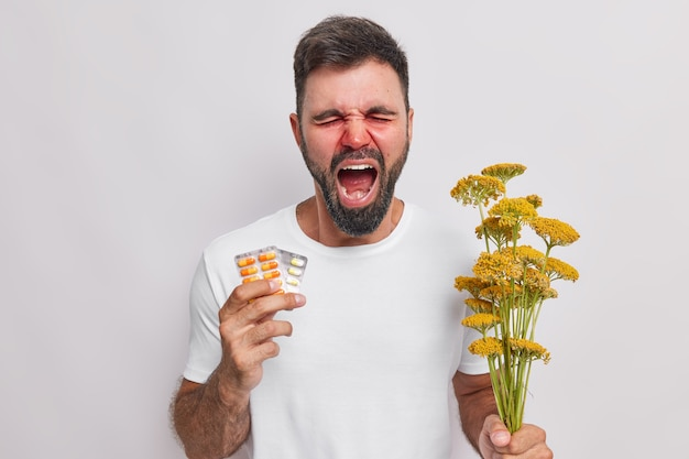 Man screams loudly suffers from seasonal allergy holds medicine and bouquet of wildflowers has stuffy nose needs good treatment poses indoor on white