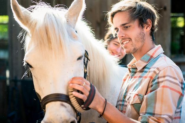 Человек, вычищающий белую лошадь