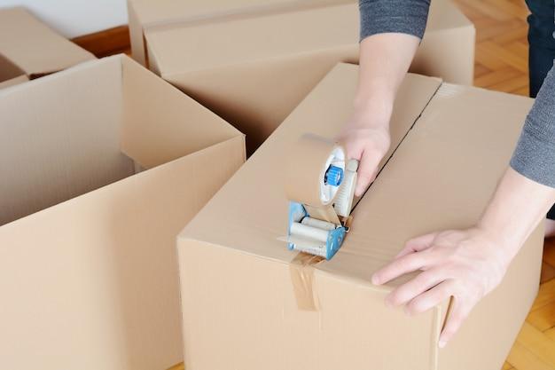 Человек, запечатывающий картонную коробку
