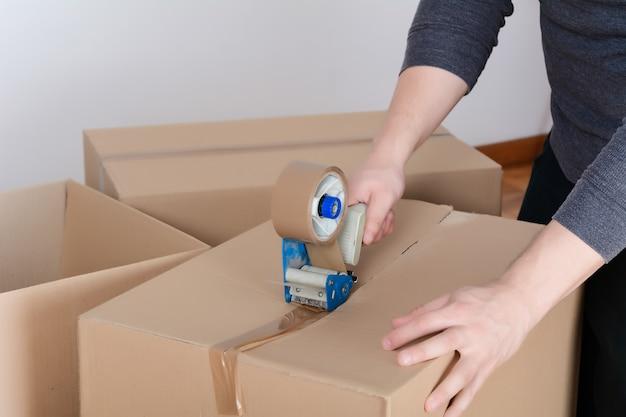 Человек, запечатывание доставки картонной коробке