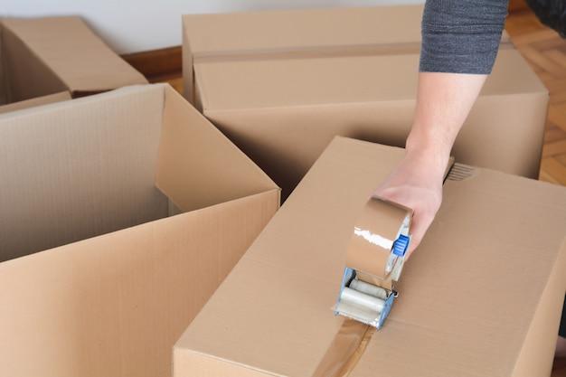 Man sealing a shipping cardboard box
