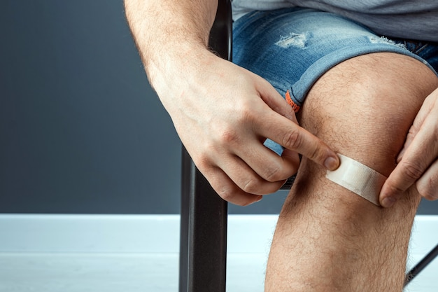 A man seals a wound on his knee with adhesive plaster close-up. ambulance, body care, knee injuries.