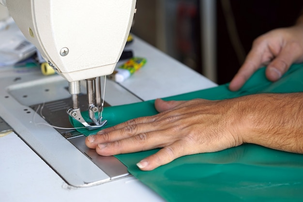 Man seamstress. men's hands behind sewing leather.