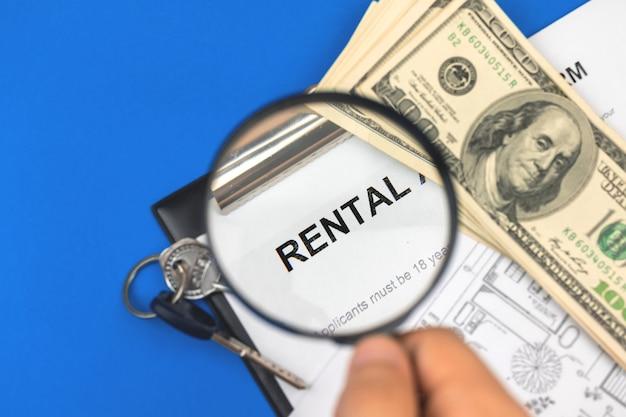 Человек ищет концепцию аренды. договор аренды и увеличительное стекло в руке. буфер обмена с документом на офисном столе с ключами от дома. фото на синем фоне