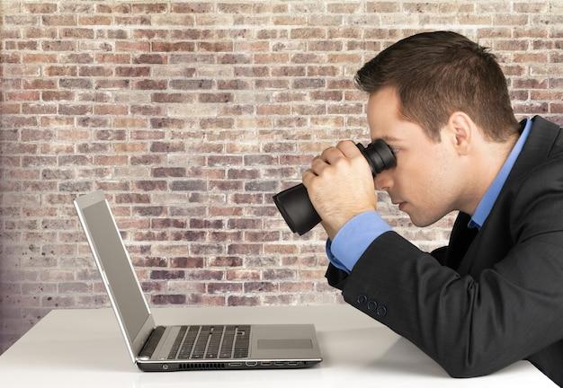노트북에서 검색 하는 남자. 쌍안경으로