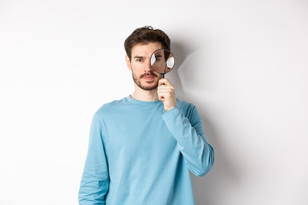 Man searching for something, looking through magnifying glass at camera, standing on white background.