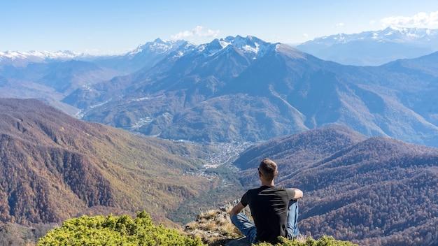 남자는 achisho 산 정상에 앉아 러시아 소치의 겨울인 krasnaya polyana를 바라보고 있습니다.