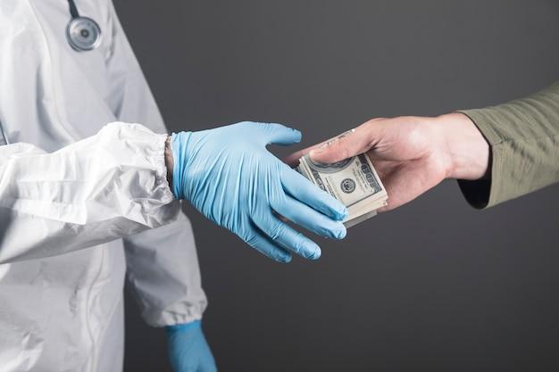 Man secretly hand over money to doctor on gray scene
