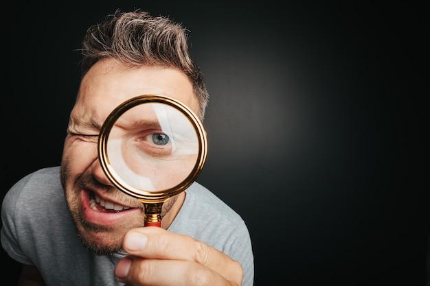 男は虫眼鏡を通して見る。大きな男の目