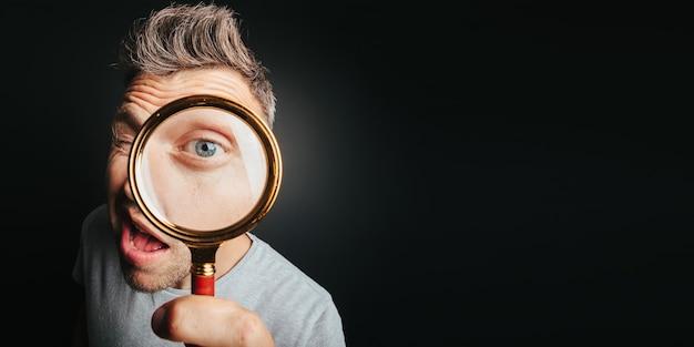 Человек видит через увеличительное стекло на черном фоне. глаз большого человека