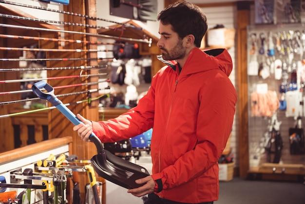 お店でシャベルを選ぶ男