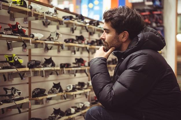 L'uomo la selezione di attacchi da sci in un negozio