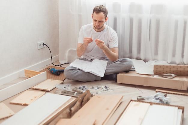 Человек самостоятельно собирает деревянную мебель в домашних условиях без мастера