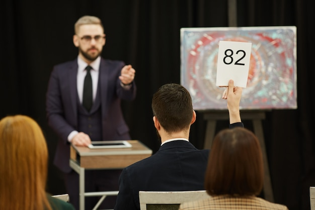 Man selling the painting at auction