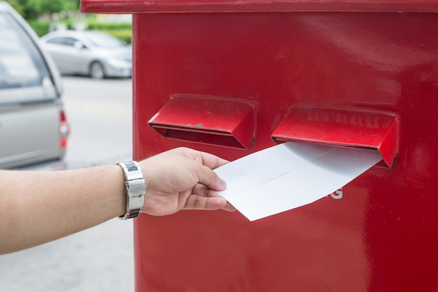 Man sending mail in the city. a man sending a letter and documents via mailbox.