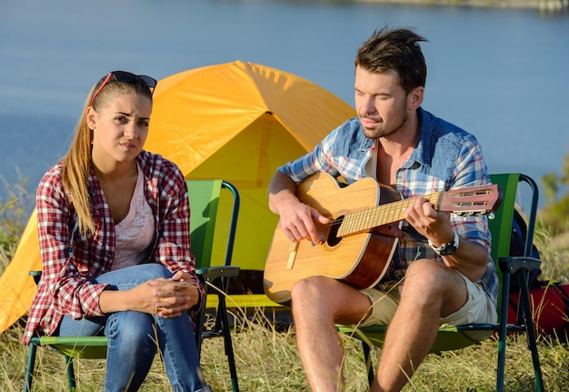 Man serenading his girlfriend on camping trip on a sunny day