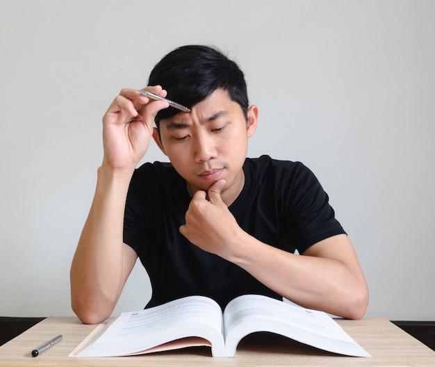 남자는 시험에 진지한 얼굴을 하고, 젊은 남자는 책상에 앉아 책을 탁자 위에 놓고 생각하고, 시험 개념