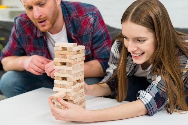 Man seriously looking at smiling girlfriend removes wooden blocks from tower