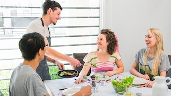 Man serving fresh cooked vegetables to her female friends at home