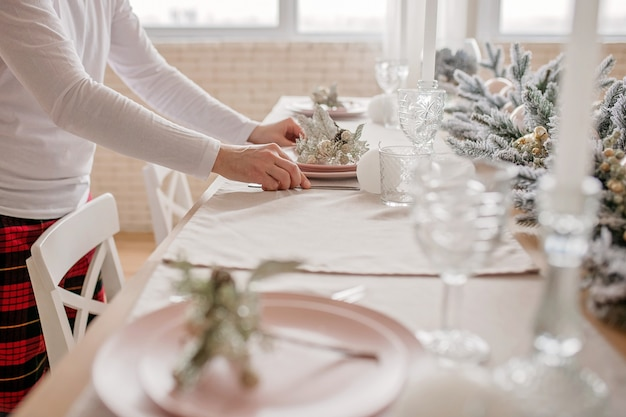 Man sets a beautiful decorated winter table