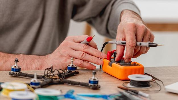 Мужчина настраивает устройство для проверки перезарядки во время ремонта квадрокоптера. крупным планом вид