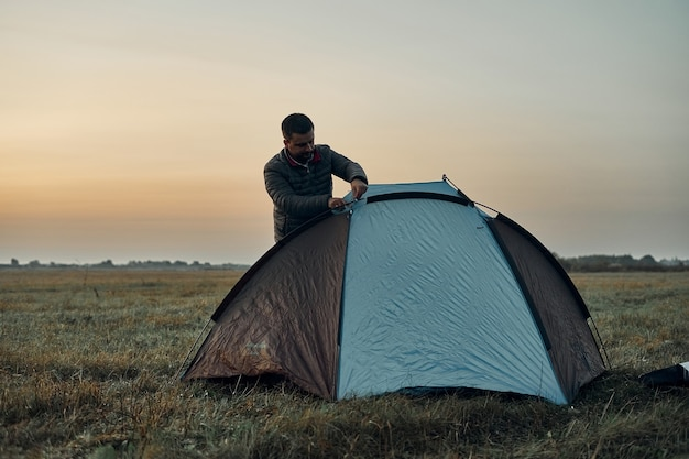 A man sets up a tent, awning at sunrise.