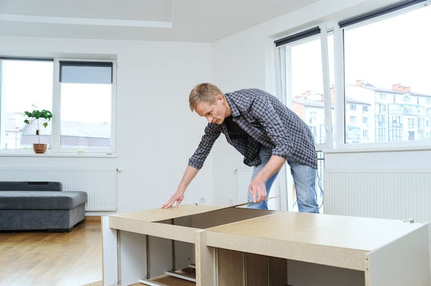 Man setting the mdf panel to the back of the dresser