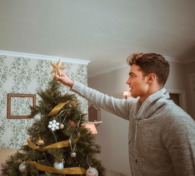 Man setting star on christmas tree top