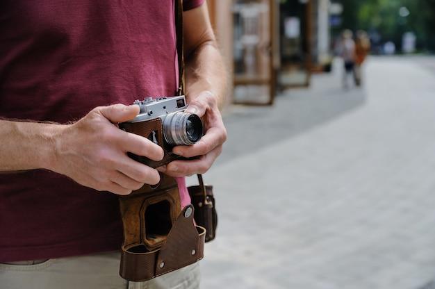 ヴィンテージカメラのレンズを設定する男