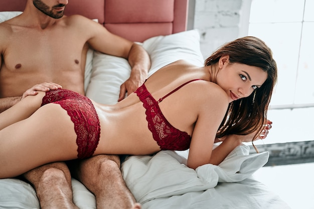 The man and sexy woman in underwear laying on the bed