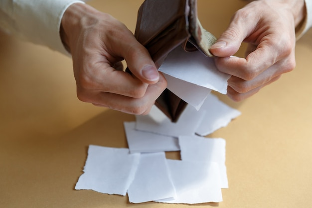 A man shakes out a paper from a wallet on a plain background