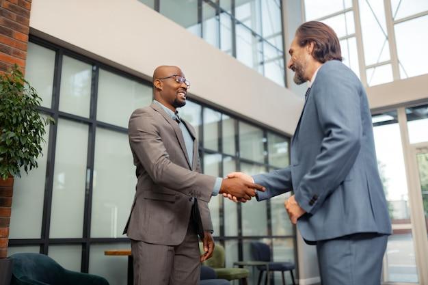 Man shaking hand. dark-skinned businessman wearing glasses shaking hand of his investor